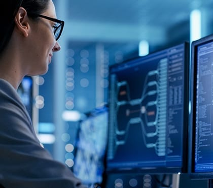 woman looking at computer screen at company that uses it managed services