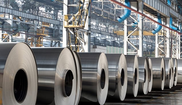 rolls of steel on ground of warehouse that uses it company