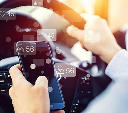 man in car looking at notifications from it consultant on phone