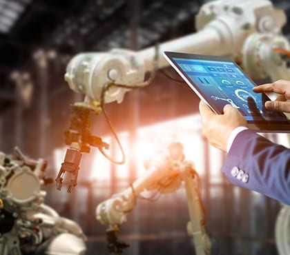 man reviewing robotic arm stats in warehouse for company that uses managed it services