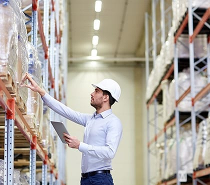 man wearing white hard hat checking inventory in warehouse for company that has it security