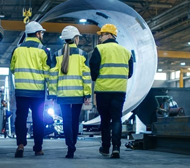 three people in safety jackets and hard hats walking through factory for company that uses it services