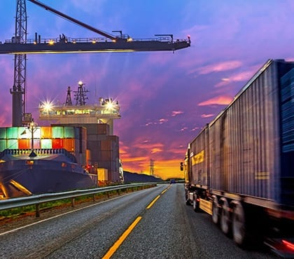 truck driving past shipping container yard