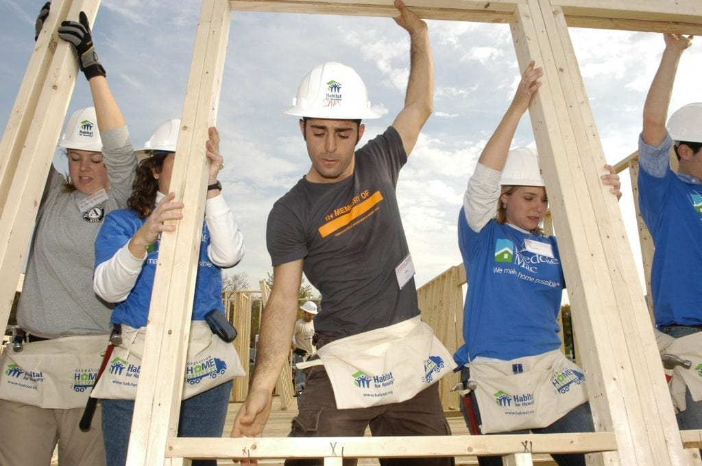 volunteers supporting a wall frame during a house build for Habitat for Humanity