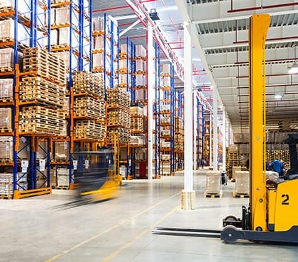 warehouse with shelves filled with pallets for company that uses managed services